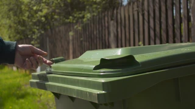 Senior retired old man throwing garbage into green recycle garbage bin video