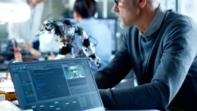 stockvideo's en b-roll-footage met senior robotics ingenieur manipuleert stem gecontroleerde robot, laptop scherm toont software met behulp van machine learning techniek. in het laboratorium van de achtergrond robotics research center. - robot engineer