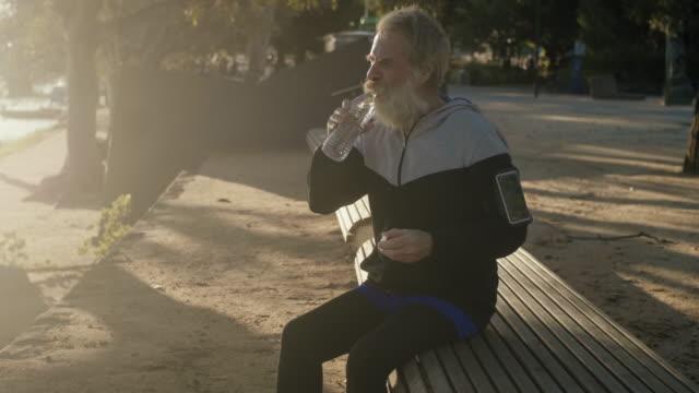 Senior runner drinking water (slow motion) video