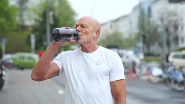 senior runner on city streets - acqua potabile video stock e b–roll