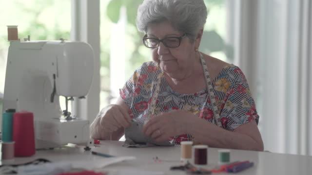 senior seamstress making mask for covid-19 in 2020 - sarta video stock e b–roll