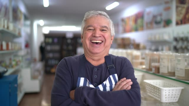 Senior seller standing with arms crossed in a natural products store