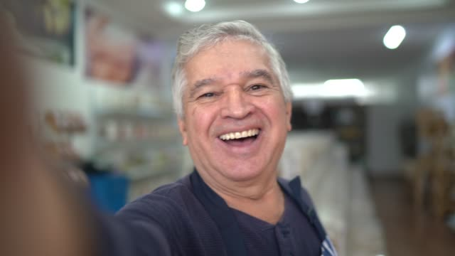 Senior seller taking a selfie while working in a natural products store