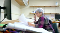 istock Senior silver-haired woman, engineer, measuring the space on the drawing of architectural project with curvimeter. 877826012