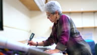 istock Senior silver-haired woman, engineer, using curvimeter when she working with architectural project 877826062