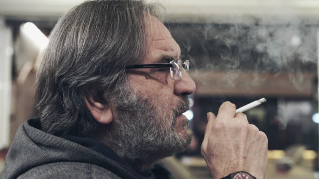 senior smoking a cigar and coughing - sigaretta video stock e b–roll