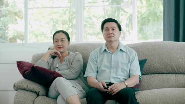 Senior Southeast Asian couple watching News in television while sitting on sofa at home living room video