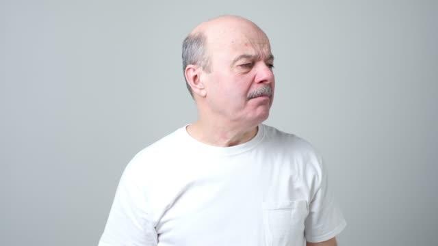 vídeos de stock e filmes b-roll de senior spanish man with disgust on his face, pinching his nose - cheiro desagradável