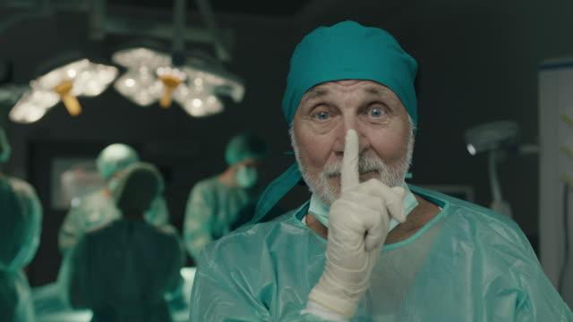 stockvideo's en b-roll-footage met senior chirurg vraagt om stil te zijn met de vinger op de lippen - stilte