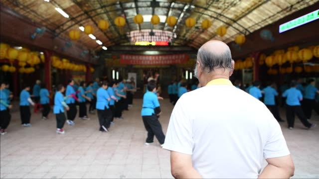 Senior Tai Chi Master watching senior students practice