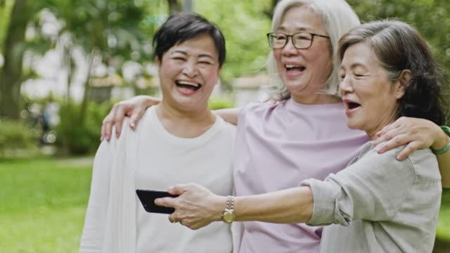 스마트폰을 보고 웃고 있는 대만 고위 여성들 - 웰빙 스톡 비디오 및 b-롤 화면