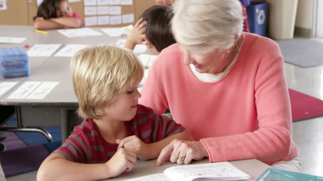 Senior teacher helps young schoolboy in class, elevated view video
