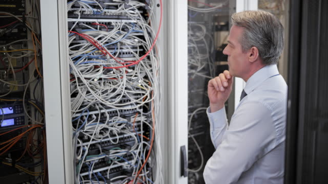 Senior technician contemplating about the cable mess in the server room