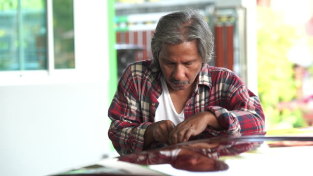 Senior technician man repairing car engine in garage