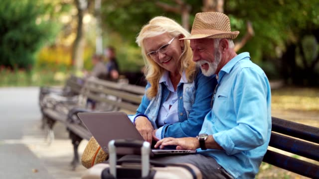 Senior tourists making video call in park Smiling senior tourists having video chat on the bench in park. baby boomers stock videos & royalty-free footage