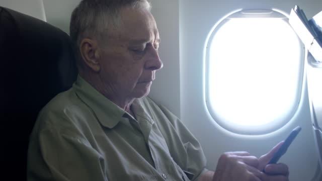 vídeos de stock e filmes b-roll de senior traveling in plane and reading news from smartphone - old men window