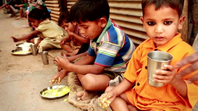 senior volunteer woman serving food to rural children - hindistan stok videoları ve detay görüntü çekimi