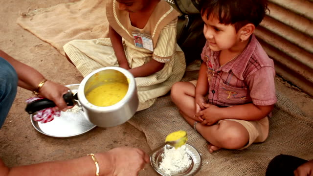 Senior Volunteer woman Serving food to Rural Children Senior Volunteer woman Serving food to Rural Children  poverty stock videos & royalty-free footage