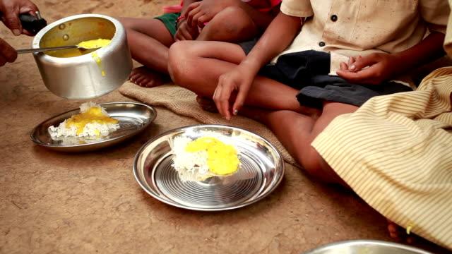 Senior mujer de voluntarios, que sirve comida para niños Rural - vídeo