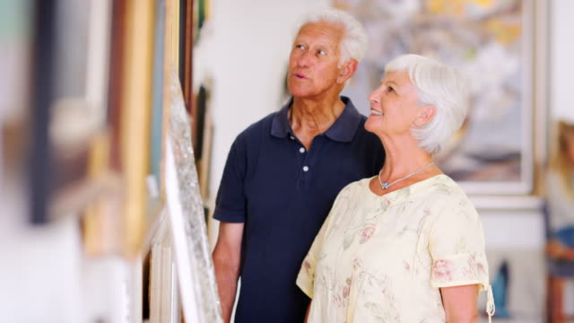 senior white couple looking at paintings in an art gallery - museo video stock e b–roll