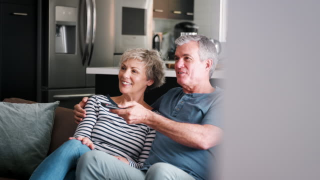 senior white couple relaxing on couch watching television - coppia anziana video stock e b–roll