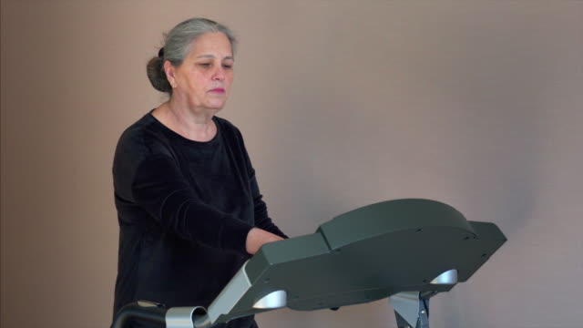senior white hair woman is change mode of treadmill before training at home. - runner rehab gym video stock e b–roll