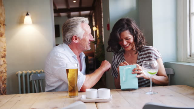 Senior white man giving a present in a gift bag to his Hispanic female friend, sitting with drinks at a table in a pub, close up, side view