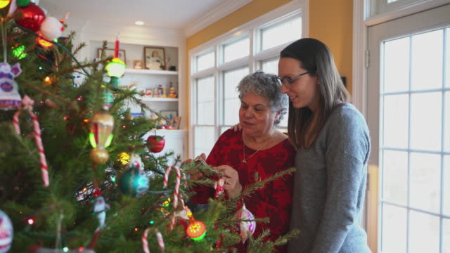 Senior woman, a mother, and her daughter decorating a Christmas Tree together in a living room.