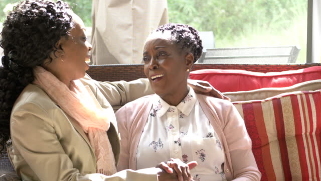 Senior woman, adult daughter sitting together conversing A senior African-American woman in her 70s is sitting in a sun room with her adult daughter, conversing, smiling, holding hands. black people stock videos & royalty-free footage