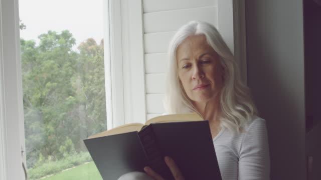 stockvideo's en b-roll-footage met senior vrouw alleen thuis - boek