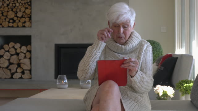Senior Woman Alone using tablet in living room