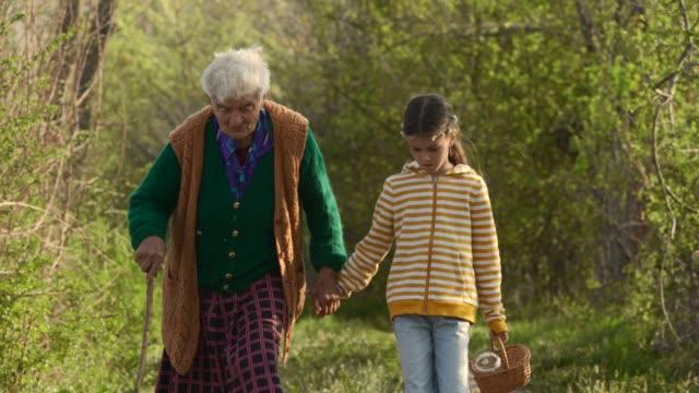 senior woman and child walking down the road. holding hands. - nonna e nipote camminare video stock e b–roll