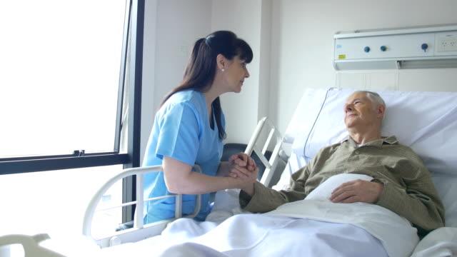 Senior woman and female nurse communicating in hospital video