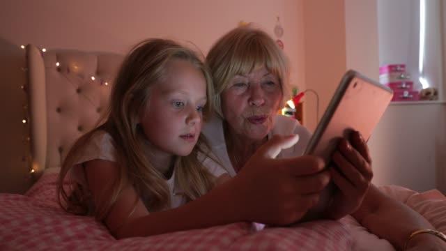 senior woman and her granddaughter using a digital tablet - kołdra filmów i materiałów b-roll