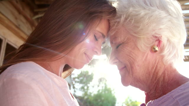 Senior woman and her loving adult daughter outdoors