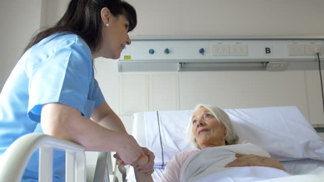 Senior woman and nurse communicating in hospital Handheld shot of senior woman and female nurse communicating in hospital. Professional is comforting patient lying in bed. Elderly woman is resting while looking at medical worker. hospital bed stock videos & royalty-free footage