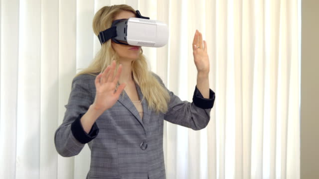 Senior woman architect or client using vr glasses to imagine or design a project standing in the office