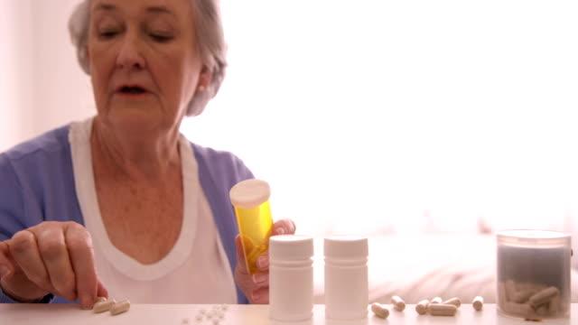 Senior woman arranging a pills video