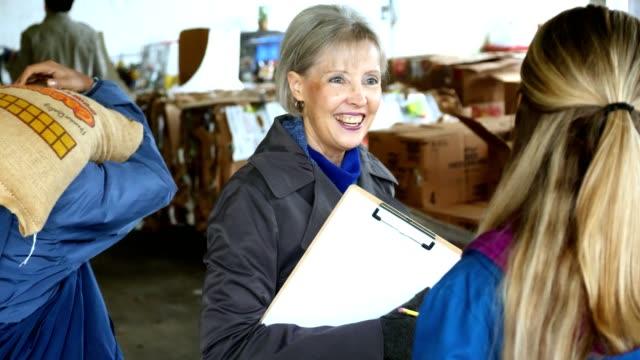 senior kvinna på en gemenskap uppsökande händelse leder volontärer - välgörenhet bildbanksvideor och videomaterial från bakom kulisserna