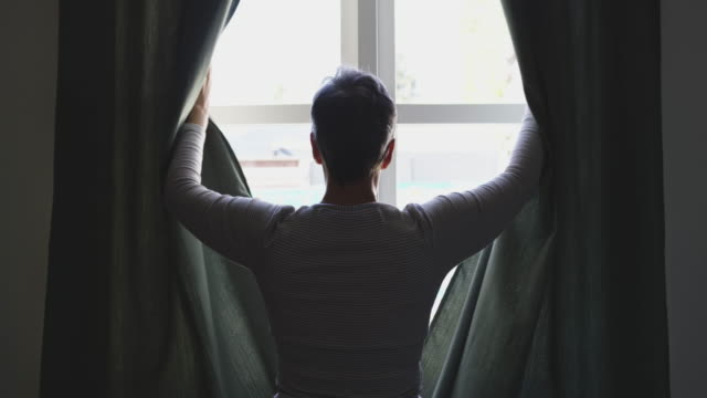 Senior woman at home alone Rear view of a senior Caucasian woman with short hair standing and drawing the curtains at home, silhouetted against the window, slow motion mental health stock videos & royalty-free footage