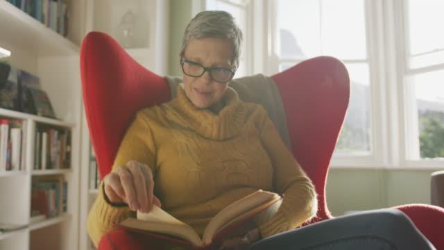 stockvideo's en b-roll-footage met senior vrouw thuis alleen - boek