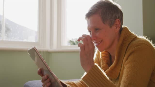 Senior woman at home alone Side view close up of a senior Caucasian woman at home, sitting in her living room using a tablet computer and smiling, backlit by sunlight from a window, slow motion short hair stock videos & royalty-free footage
