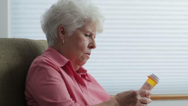 Senior woman at home reading prescription bottle video