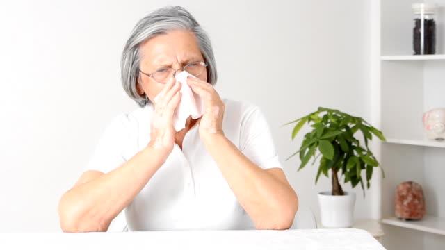 Senior woman blowing nose. video