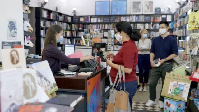 senior kvinna köper böcker på bokhandeln under pandemi - konstkultur och underhållning bildbanksvideor och videomaterial från bakom kulisserna
