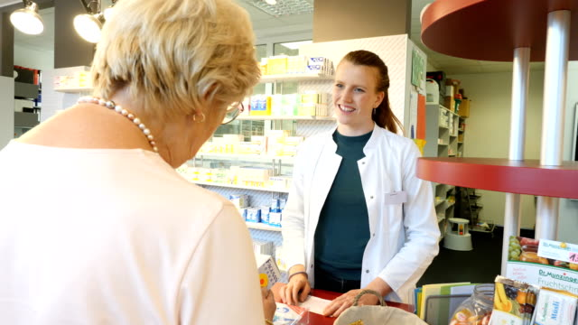 Senior woman buying medicine from pharmacist