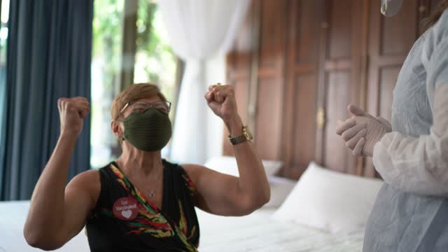 Senior woman celebrating after being vaccinated at home - wearing face mask video