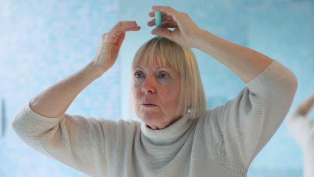 senior frau überprüfen hairline für haarausfall - kosmetische behandlung stock-videos und b-roll-filmmaterial