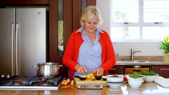 senior woman chopping vegetable in kitchen 4k - 60 69 anni video stock e b–roll