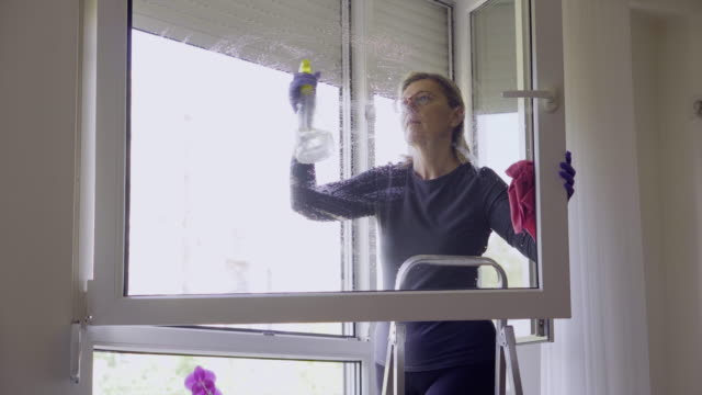 Bидео Senior woman cleaning window at home During Coronavirus